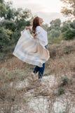 Привлекательная молодая женщина идущ снаружи создает программу-оболочку в теплом одеяле стоковые фото