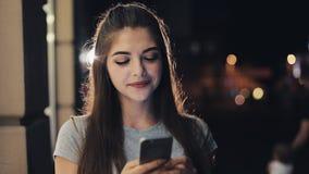 Привлекательная молодая женщина используя smartphone стоя на улице городка ночи реагируя счастливо к сообщению самомоднейше сток-видео