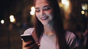 Привлекательная молодая женщина используя smartphone стоя на улице городка ночи реагируя счастливо к сообщению самомоднейше акции видеоматериалы