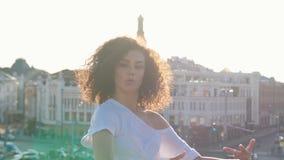 Привлекательная молодая женщина мулата с танцами вьющиеся волосы и flirting с телезрителем - смотрящ в камере акции видеоматериалы