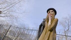 Привлекательная молодая женщина наслаждаясь ее снаружи времени в парке с заходом солнца E Красивая молодая женщина в шляпе идя вн сток-видео