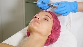 Процедуры спа Привлекательная молодая женщина на салоне красоты Beautician прикладывая лицевую маску к женскому клиенту Терапия с сток-видео