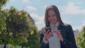 Привлекательная молодая женщина на солнечных улицах города и беседовать с друзьями, радостной девушкой хипстера используя мобильн акции видеоматериалы