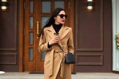 Привлекательная молодая женщина нося бежевое пальто, черный свитер, имеет сумку и солнечные очки, смотрят в сторону, выпивают на  стоковая фотография