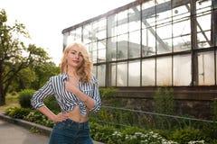 Привлекательная молодая женщина нося striped блузку, представляя около g стоковая фотография