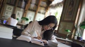 Привлекательная молодая женщина пишет, книга чтения для юриста видеоматериал