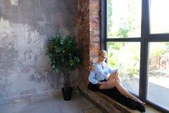 Привлекательная молодая женщина представляет с улыбкой и сидит на силле окна Стоковая Фотография