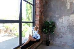 Привлекательная молодая женщина представляет с улыбкой и сидит на силле окна Стоковые Изображения