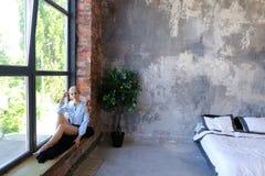 Привлекательная молодая женщина представляет с улыбкой и сидит на силле окна Стоковое Изображение