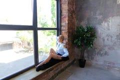 Привлекательная молодая женщина представляет с улыбкой и сидит на силле окна Стоковая Фотография RF