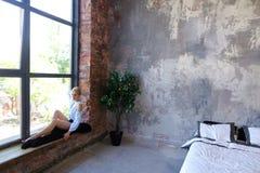 Привлекательная молодая женщина представляет с улыбкой и сидит на силле окна Стоковые Фото