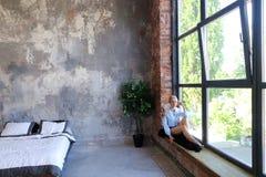 Привлекательная молодая женщина представляет с улыбкой и сидит на силле окна Стоковое Фото