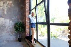 Привлекательная молодая женщина представляет с улыбкой и стоит на sil окна Стоковое Изображение