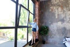Привлекательная молодая женщина представляет с улыбкой и стоит на sil окна Стоковые Изображения RF