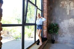 Привлекательная молодая женщина представляет с улыбкой и стоит на sil окна Стоковое Фото