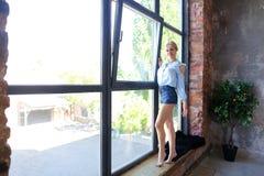 Привлекательная молодая женщина представляет с улыбкой и стоит на sil окна Стоковая Фотография