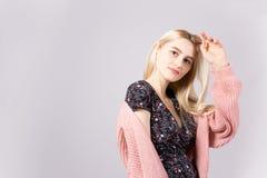 Привлекательная молодая женщина представляя над серой предпосылкой стоковые фото