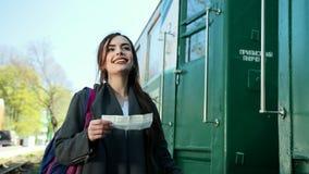 Привлекательная молодая женщина путешествует поездом, взглядами на купленном билете для отключения и ищет номер его акции видеоматериалы