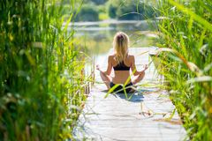Привлекательная молодая женщина работая и сидя в pos лотоса йоги стоковая фотография