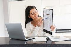 Привлекательная молодая женщина работая с ноутбуком стоковые фотографии rf