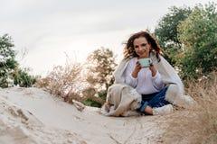 Привлекательная молодая женщина сидящ снаружи создает программу-оболочку в теплом одеяле с большой чашкой кофе стоковое фото