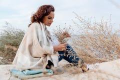 Привлекательная молодая женщина сидящ снаружи создает программу-оболочку в теплом одеяле стоковые изображения