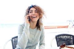 Привлекательная молодая женщина сидя на таблице кафа и говоря на мобильном телефоне Стоковые Фотографии RF