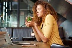 Привлекательная молодая женщина сидя на чае кафа выпивая стоковые фотографии rf