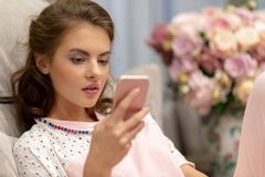 Привлекательная молодая женщина смотря ее умный телефон дома стоковое изображение rf