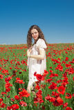 Привлекательная молодая женщина стоя в поле мака стоковая фотография