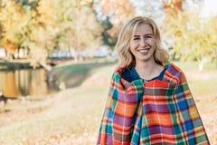 Привлекательная молодая женщина с вьющиеся волосы в оболочке в теплом одеяле и идти в парк осени снаружи стоковые фотографии rf