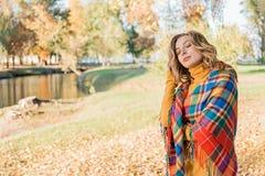 Привлекательная молодая женщина с вьющиеся волосы в оболочке в теплом снаружи одеяла стоковые фото