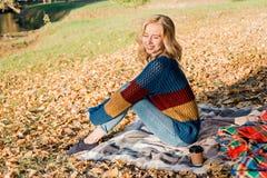 Привлекательная молодая женщина с вьющиеся волосы сидит на теплом снаружи одеяла стоковые фото