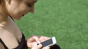 Привлекательная молодая женщина читает ленту новостей на smartphone на лужайке стадиона сток-видео