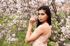 Привлекательная молодая красивая дама, наслаждаясь цветками цветения сливы весны стоковые изображения