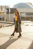 Привлекательная молодая модель с вьющиеся волосы в солнечных очках нося tre стоковая фотография