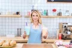 привлекательная молодая официантка держа milkshakes в пластичных чашках и усмехаться Стоковые Фотографии RF
