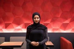 Привлекательная мусульманская женщина в черном hijab смотря камеру с красной крутой предпосылкой стоковое изображение
