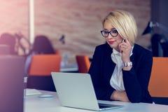 Привлекательная очаровательная белокурая бизнес-леди говоря на черни пока сидящ на столе офиса работая на компьтер-книжке стоковая фотография rf