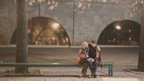 Привлекательная пара в влюбленности обнимает и наслаждается интимный момент совместно, против фона светов города сток-видео