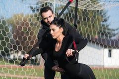 Привлекательная пара делая Trx связывает тренировку в парке Стоковые Фото
