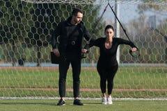 Привлекательная пара делая Trx связывает тренировку в парке Стоковая Фотография RF