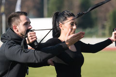 Привлекательная пара делая Trx связывает тренировку в парке Стоковые Изображения RF