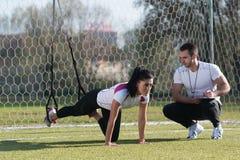 Привлекательная пара делая Trx связывает тренировку в парке Стоковая Фотография