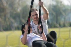 Привлекательная пара делая Trx связывает тренировку в парке Стоковое Фото