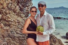 Привлекательная пара, кокос владениями при трубка, стоя на пляже около больших камней рифа, наслаждается каникулами на красивом Стоковое Фото
