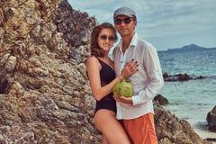 Привлекательная пара, кокос владениями при трубка, стоя на пляже около больших камней рифа, наслаждается каникулами на красивом Стоковая Фотография RF