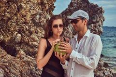 Привлекательная пара, кокос владениями при трубка, стоя на пляже около больших камней рифа, наслаждается каникулами на красивом Стоковые Изображения