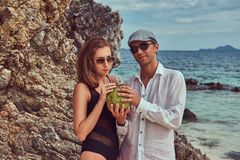 Привлекательная пара, кокос владениями при трубка, стоя на пляже около больших камней рифа, наслаждается каникулами на красивом Стоковая Фотография