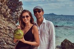 Привлекательная пара, кокос владениями при трубка, стоя на пляже около больших камней рифа, наслаждается каникулами на красивом Стоковое Изображение